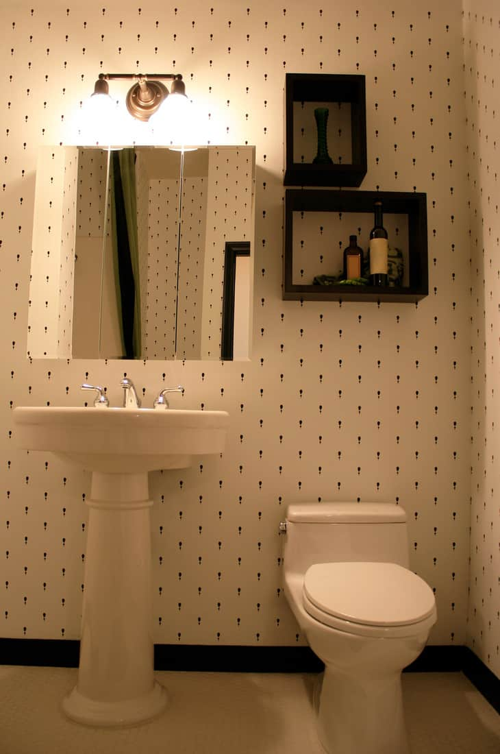 Profile of a cream colored bathroom, complete with sink, mirror, and toilet.