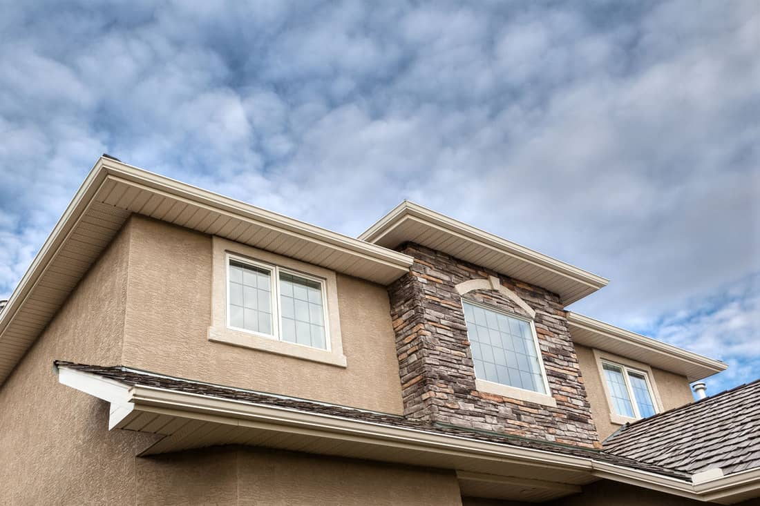 Roofline showing windows, brick stones, gutter, soffit, stucco wall, Stucco Vs Siding - What You Need To Know