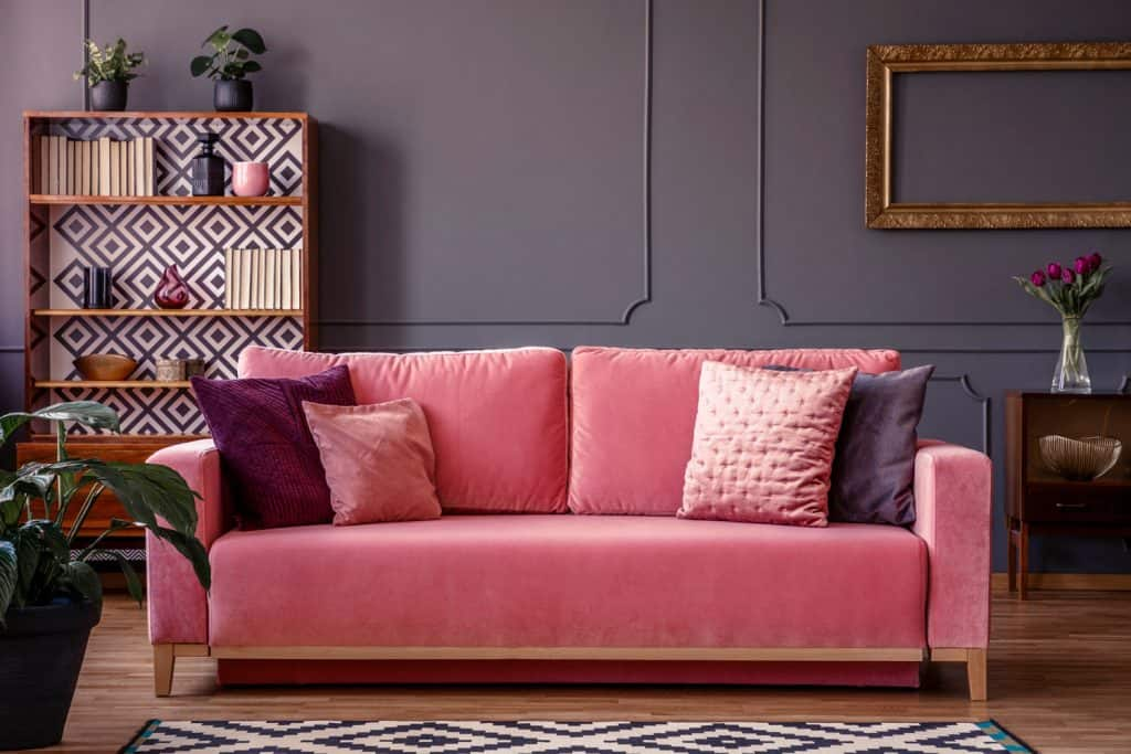 Satin pillows on a pink velvet sofa in a luxurious living room interior