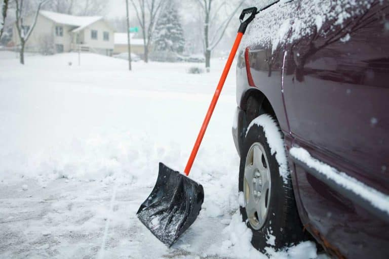 Shovel on driveway during winter snow, When To Salt The Driveway - Before Or After Snow?