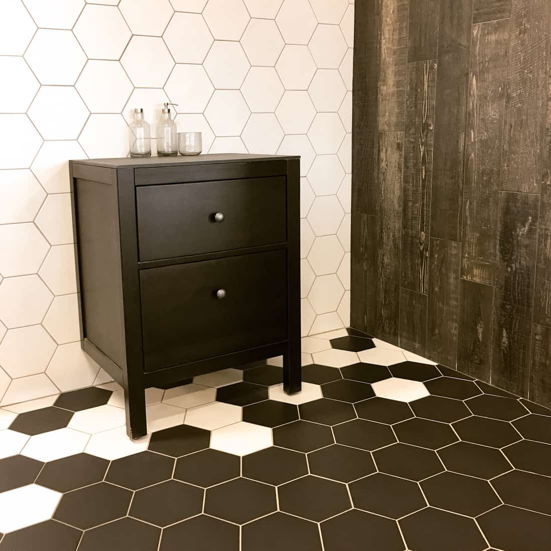 Spacious bathroom with tiled floor and wall, and black drawer unit. Contemporary design.