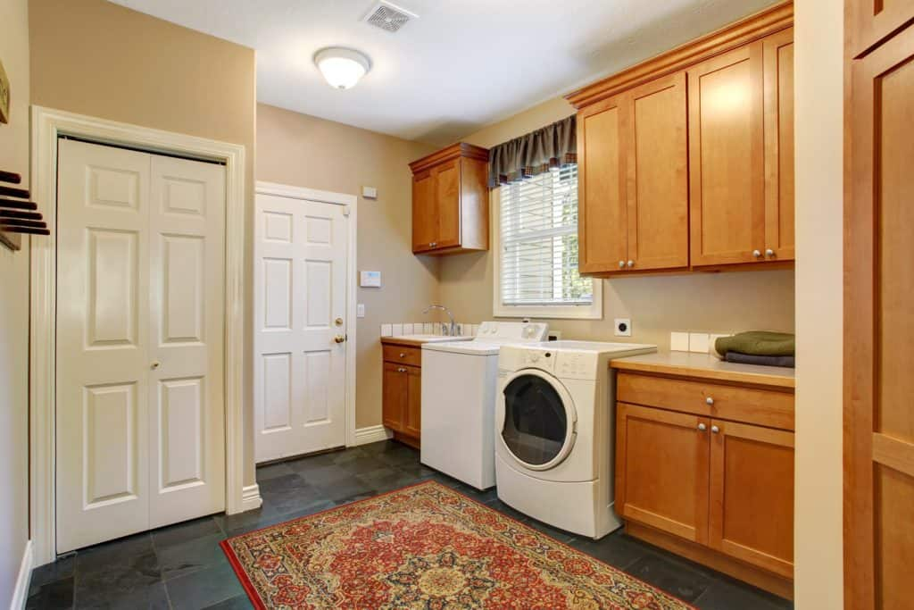 Spacious laundry room interior with dark tiles