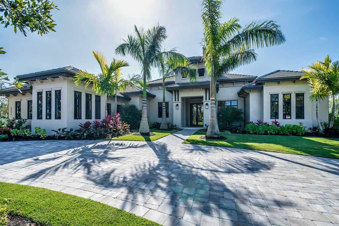 Stunning home with grand entrance, palm trees and stone circle driveway