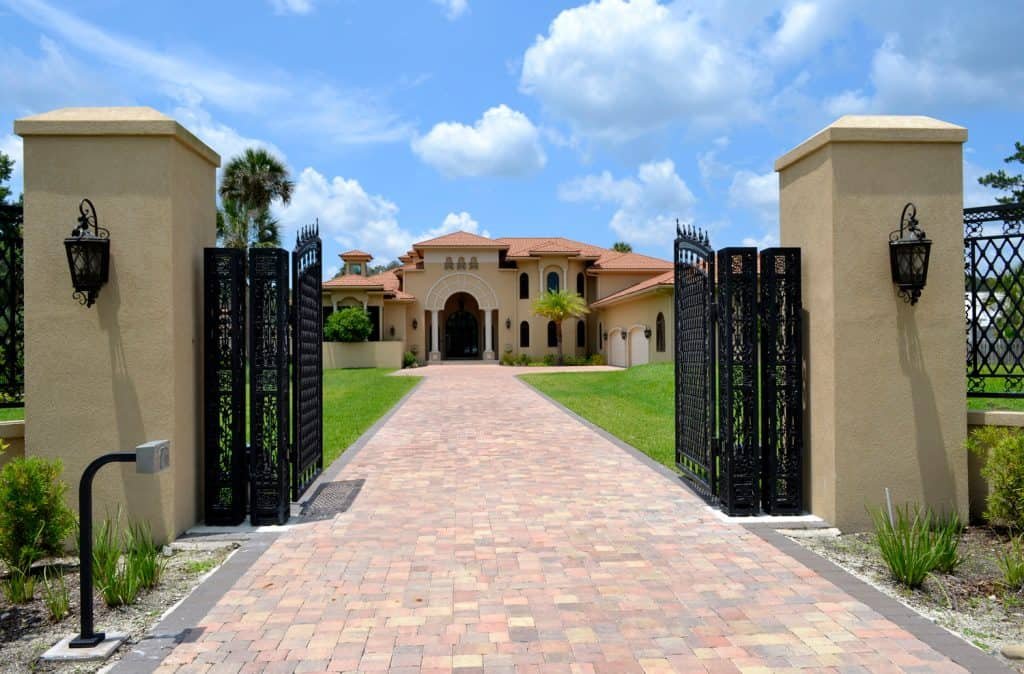 The driveway entrance and open gate to large Florida home