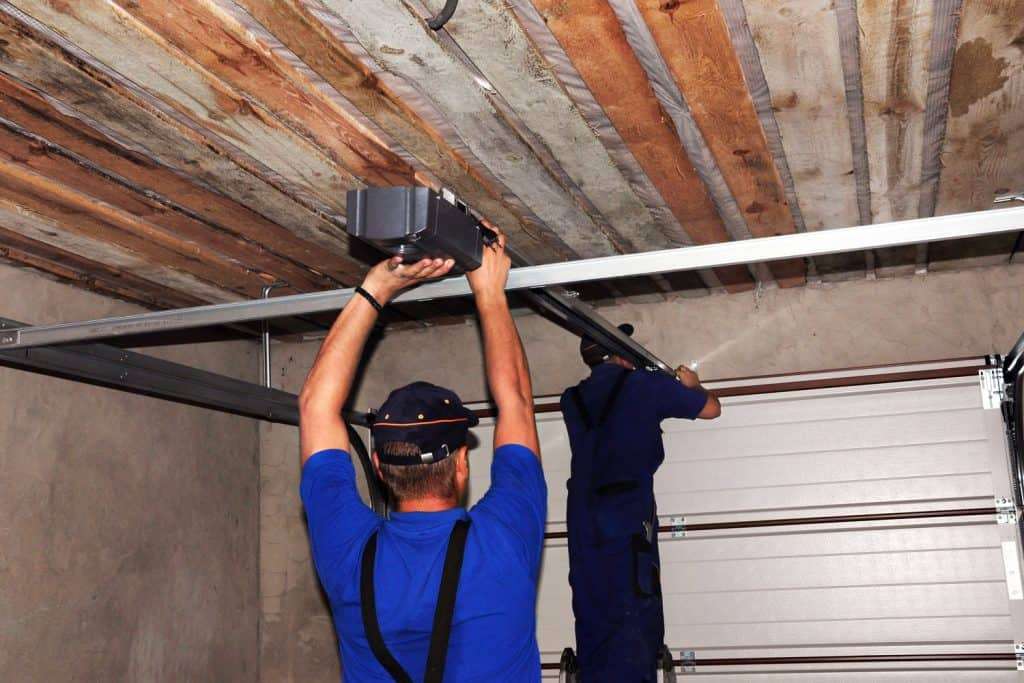 Two contractors installing a garage door opener