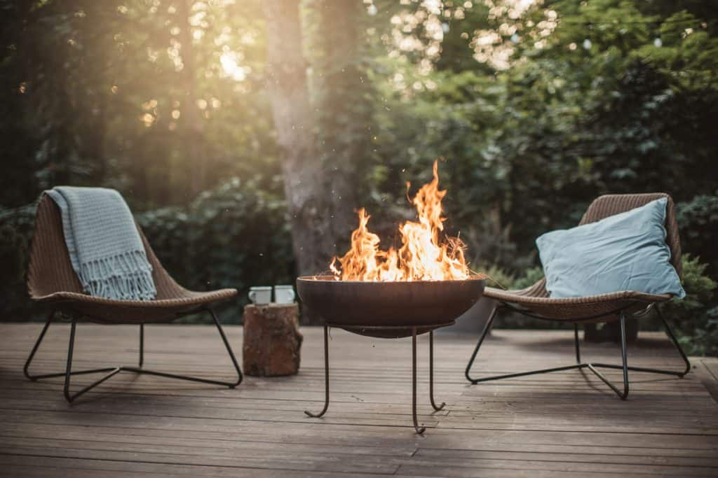 Two rattan chairs with a fireplace for warmth on the center