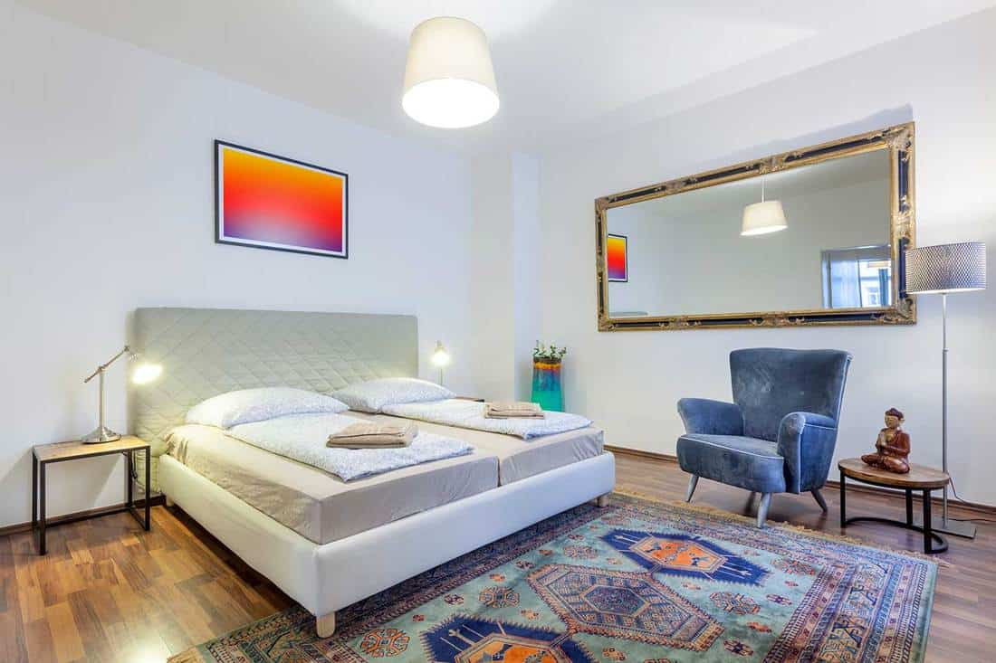 Very modern and elegant bedroom with a king sized bed, carpet, bedside tables, a large wall mirror and armchair