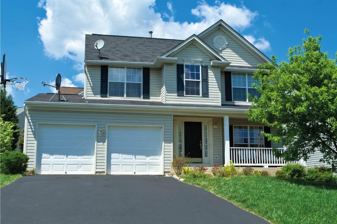 Vinyl Siding Single Family Suburban House with open graded tarmac driveway