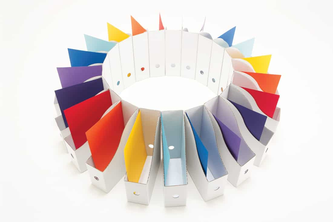 White box files containing colourful paperwork arranged in a circle.