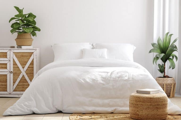 White cozy farmhouse bedroom interior, with long and narrow white comforter, How To Hide A Box Spring - Even Without A Bed Skirt!