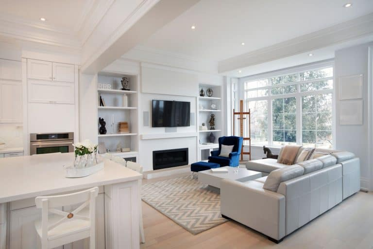White modern interior living room with a white sectional sofa, white dividers, and a wall mounted TV, 9 Captivating Layouts For A Living Room With A Large Window