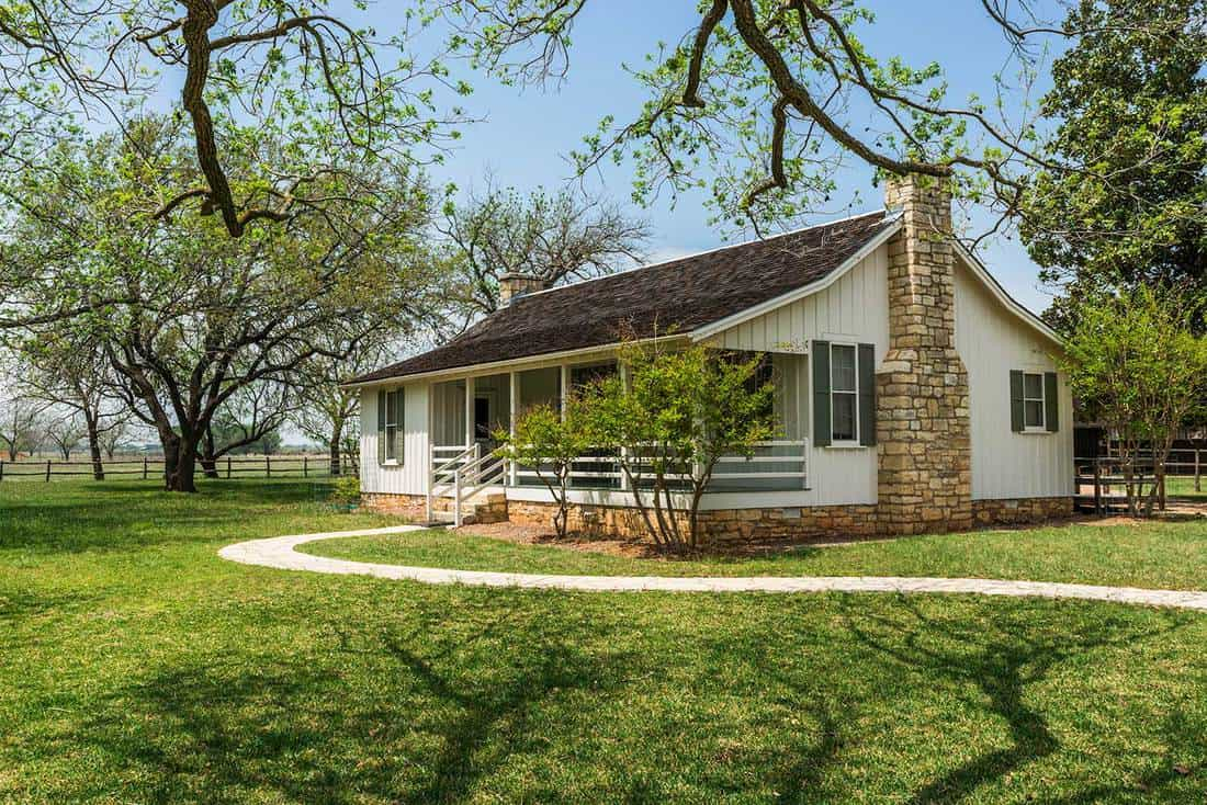 White ranch home with chimney and large yard