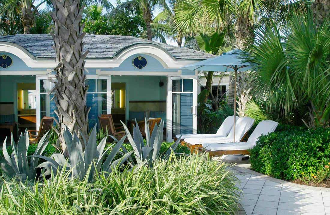 Wide angle shot of a beach bungalow with patio and lounge chairs
