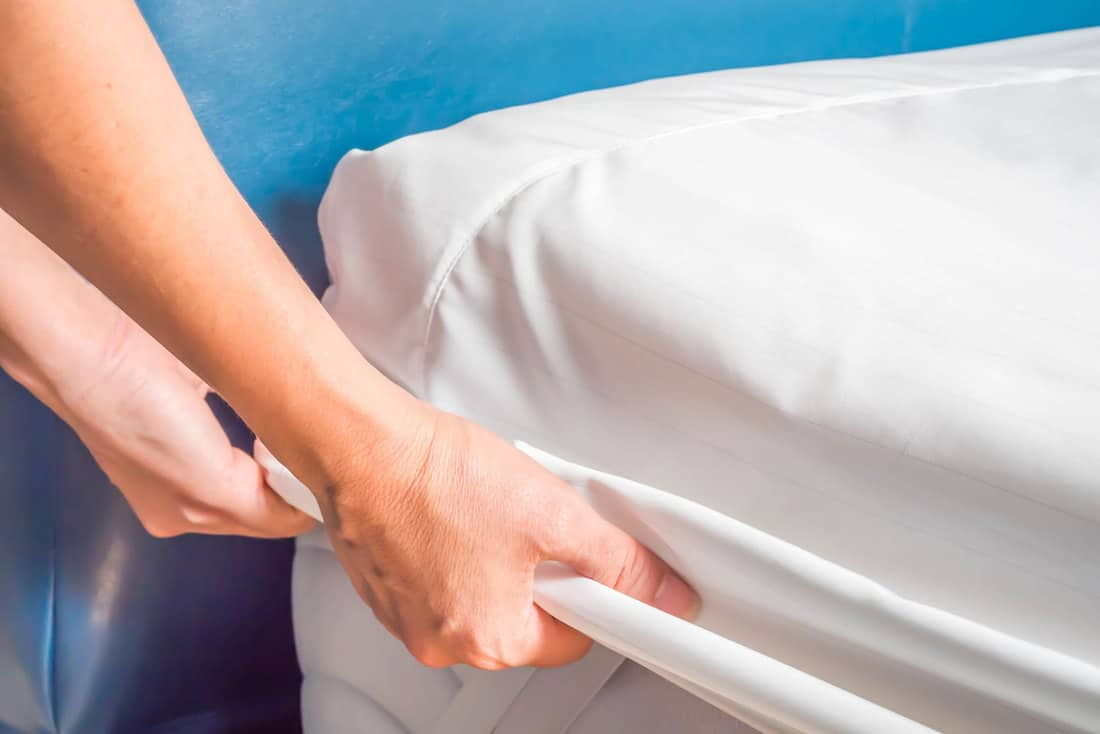 Woman is putting the bedding cover or mattress pad on the bed or putting off for cleaning process, How To Keep A Mattress Cover From Sliding [8 Nifty Techniques!]