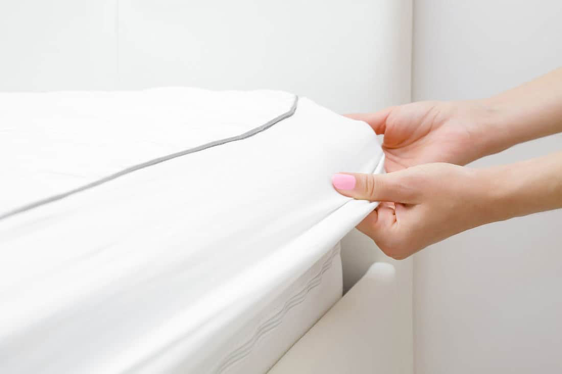 Woman's hands changing white mattress cover