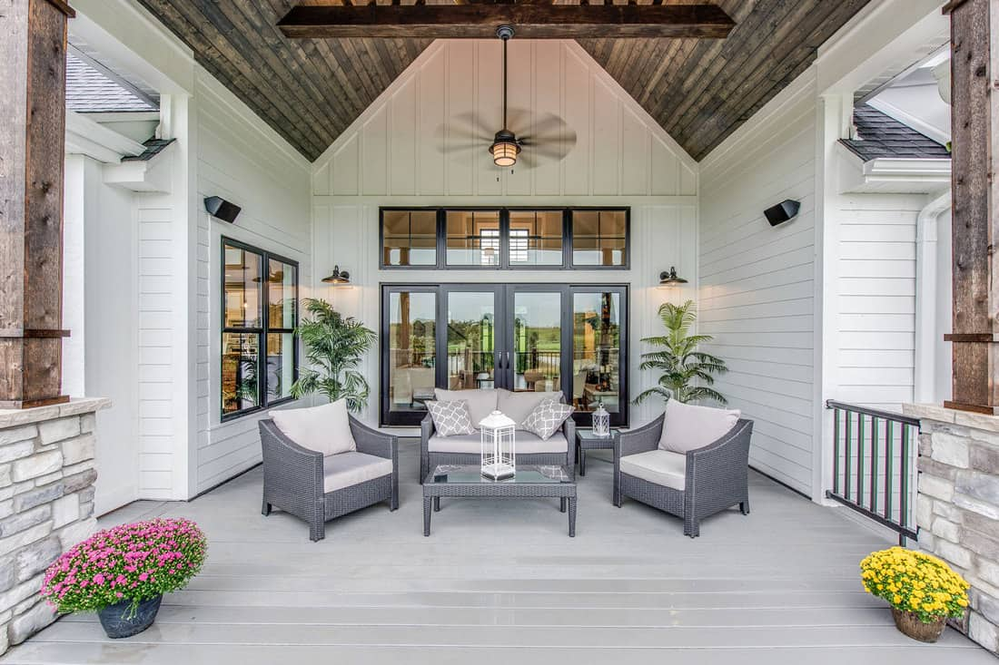 Wood panel vaulted covering on outdoor gathering area of new home, Which Outdoor Ceiling Fan Moves The Most Air? [5 Options Explored]