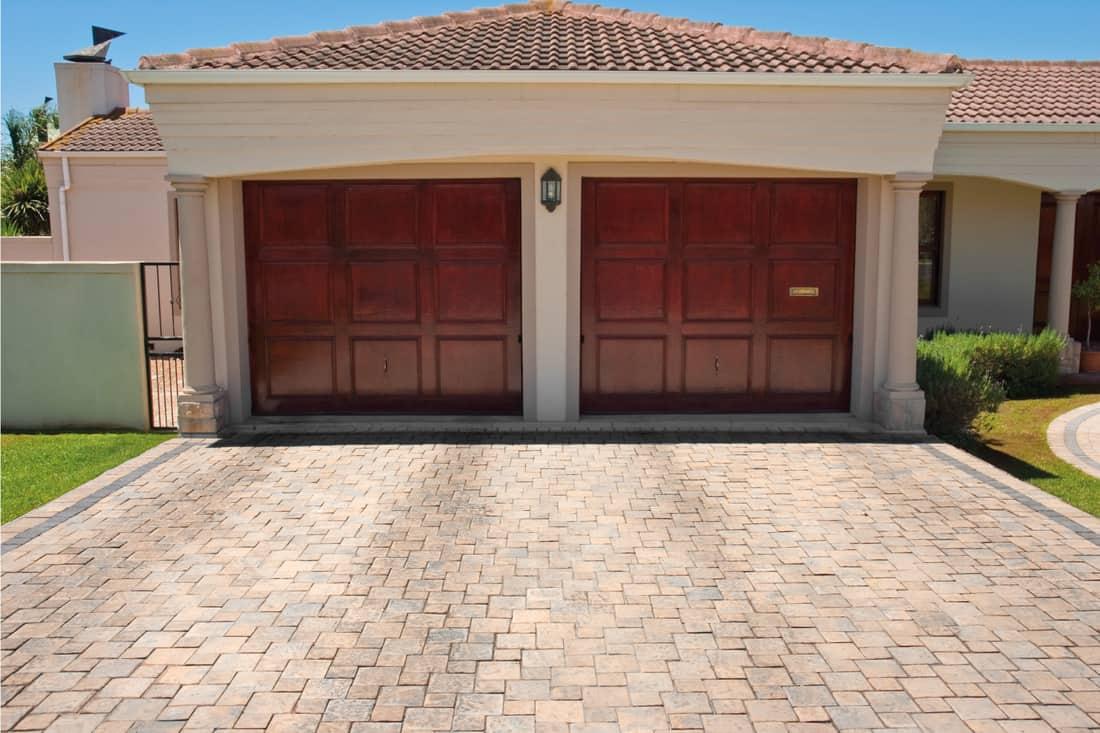 Wooden brown double garage doors, paved driveway