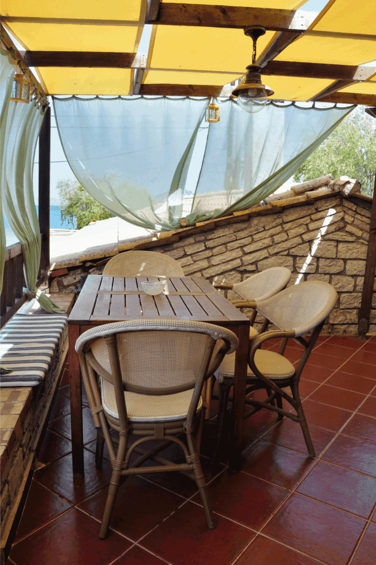 Wooden table and chairs, veranda with drapes and sea view. overhead sun shields and billowing drapes