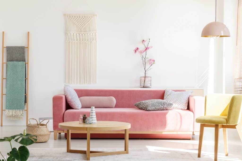 Yellow chair next to pink sofa and wooden table in pastel living room interior with flowers. Real photo