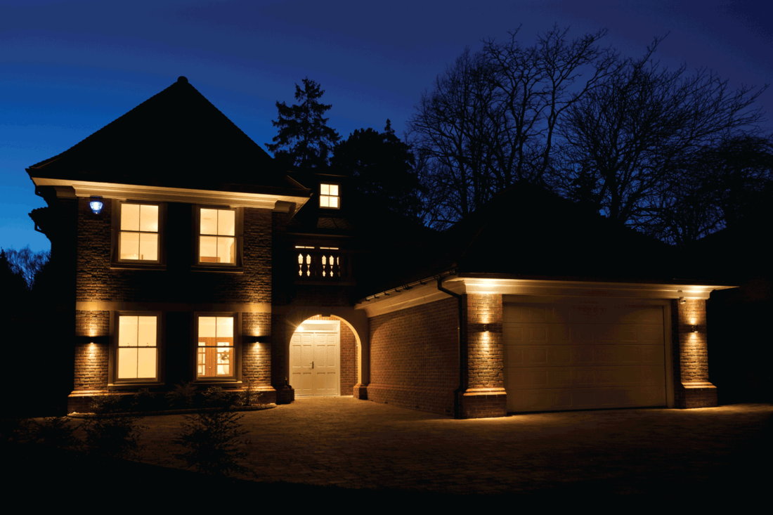 a beautiful villa taken at dusk with all interior and external lights switched on