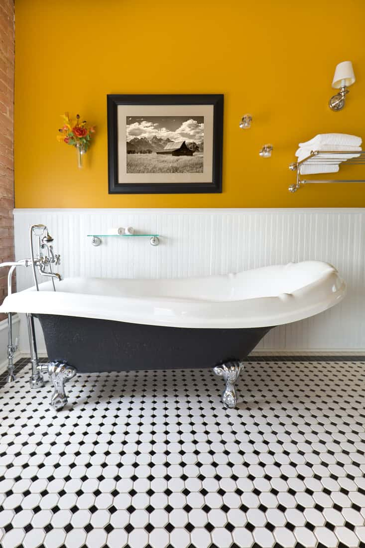 a claw foot bath tub and black and white tile pattern on the floor.