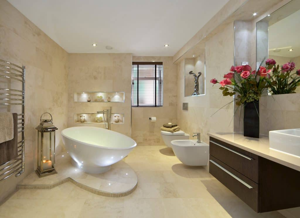 a modern bathroom in an expensive new home with a tear-drop shaped bath (full of water) sitting on a marble plinth.