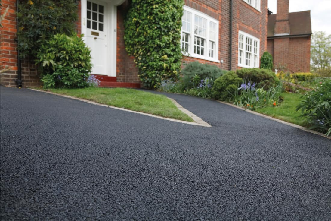 asphalt driveway in front of a brick wall house
