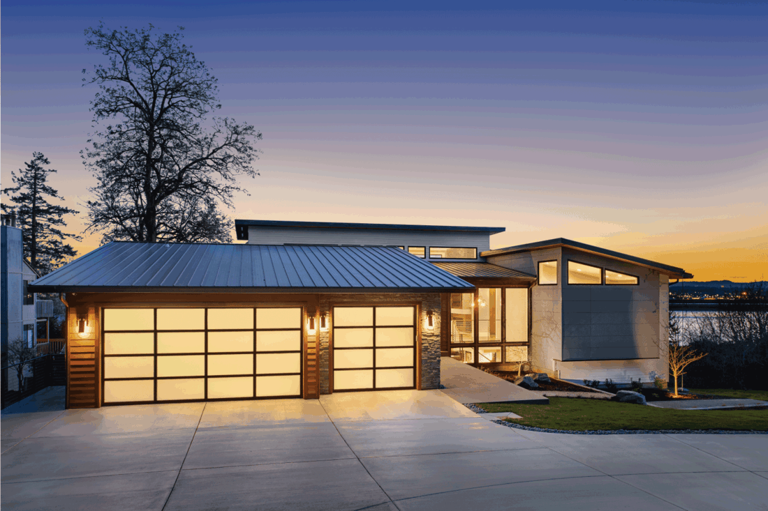 facade of home with manicured lawn, and backdrop of trees and dark blue sky. ambient backlit design garage doors