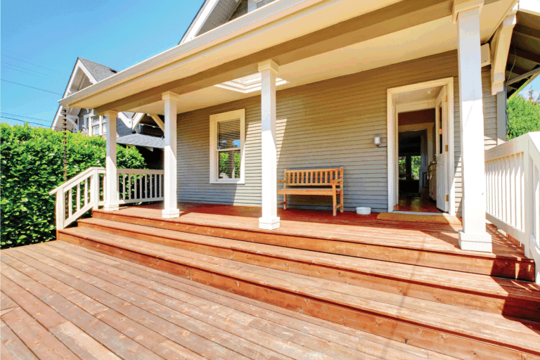 front porch of small grey house with wooden bench. 15 Incredible Front Porch Bench Ideas