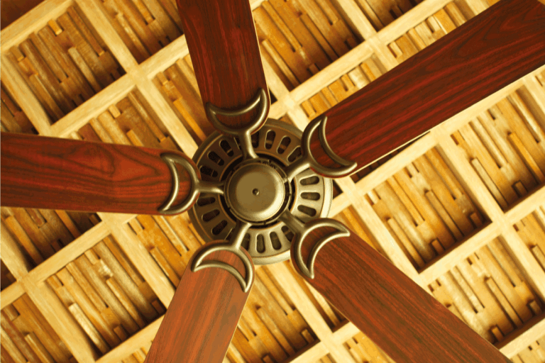 image of a ceiling fan in a holiday hotel resort with wood blades. How Many Porch Ceiling Fans Do You Need