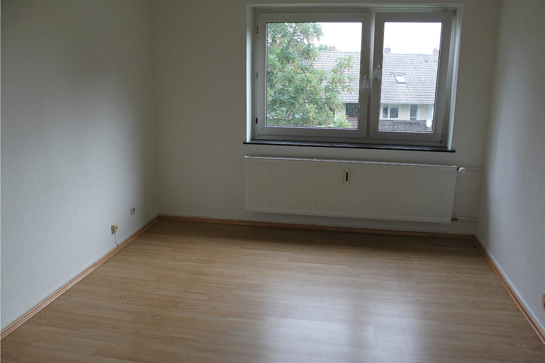 laminate flooring inside an empty laundry room with windows