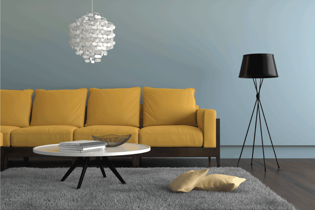 living room showing a yellow orange sofa, with a lamp, ornate pendant and a table with decoration