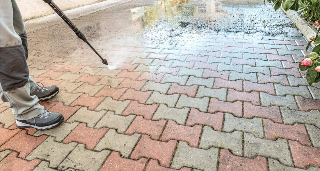 man cleaning the entrance driveway with high pressure washer