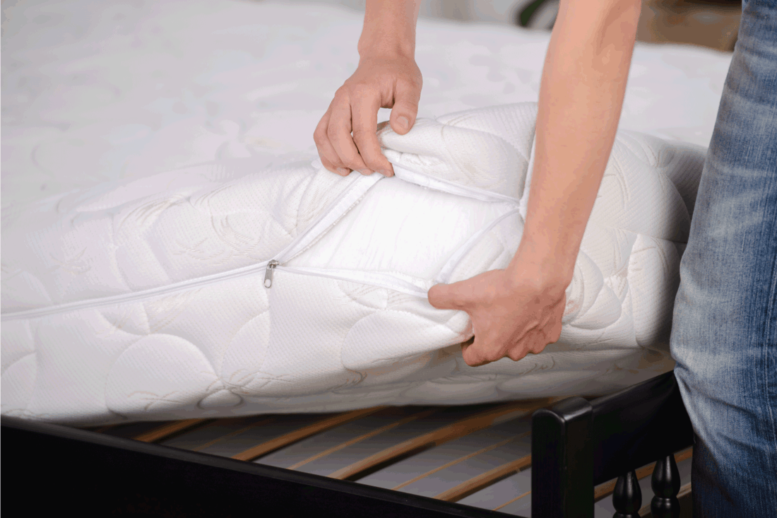 man installing white mattress cover
