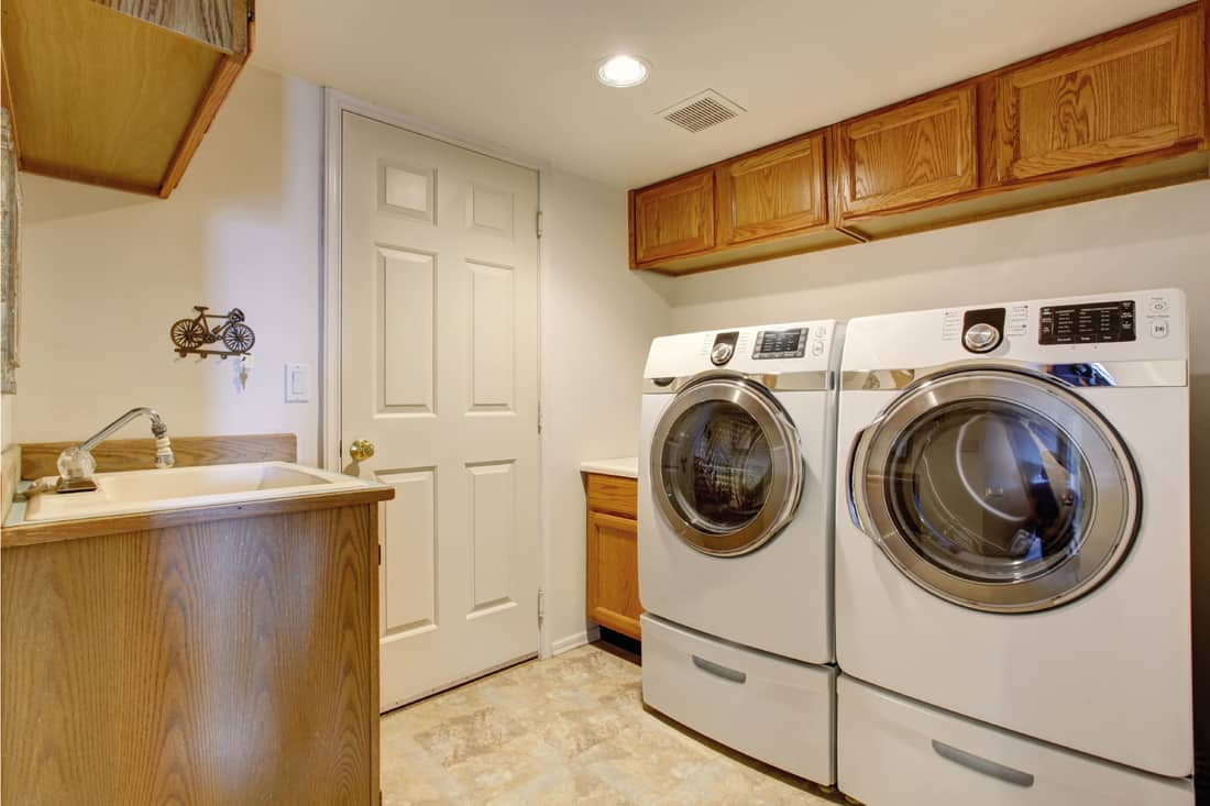 modern laundry with wooden accents for cabinets and sink, washer and dryer