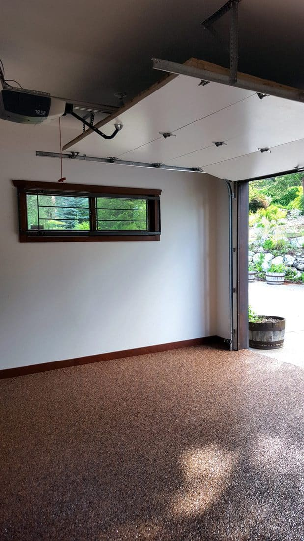 nside of well maintained and modern garage . Inside looking out. New stone epoxy floor. Fir baseboards and trim. Security bars on window. Overhead automatic garage door open.