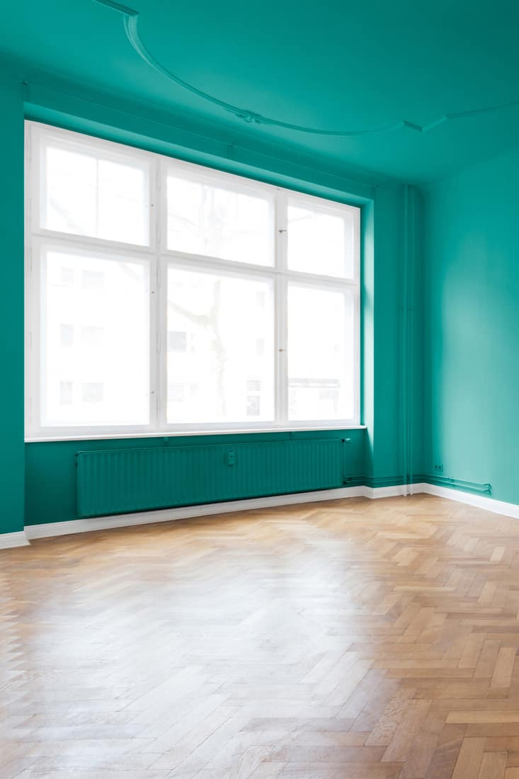 renovated room with mint green walls and parquet floor