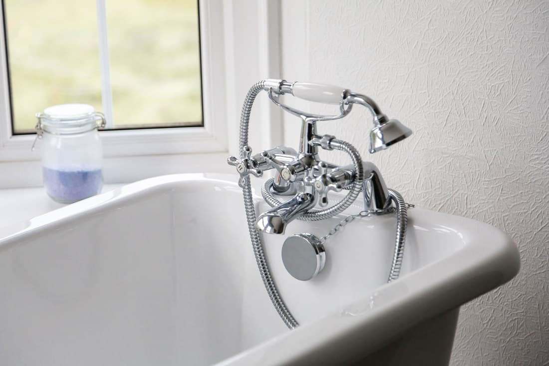 retro watertap on Bathtub in front of window closeup