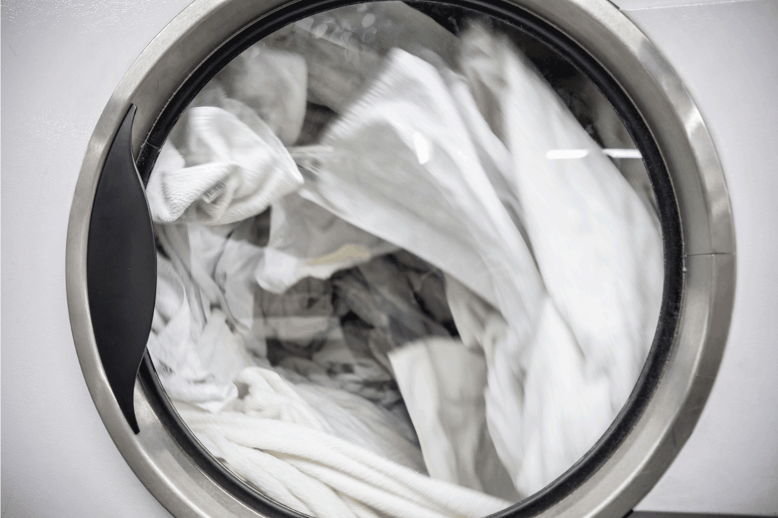 white clothes inside a laundry washer spinning