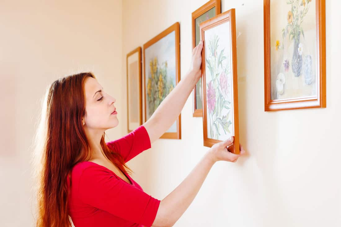 woman in red hanging the art pictures on wall at home, 7 Tips To Hang Picture Frames Evenly