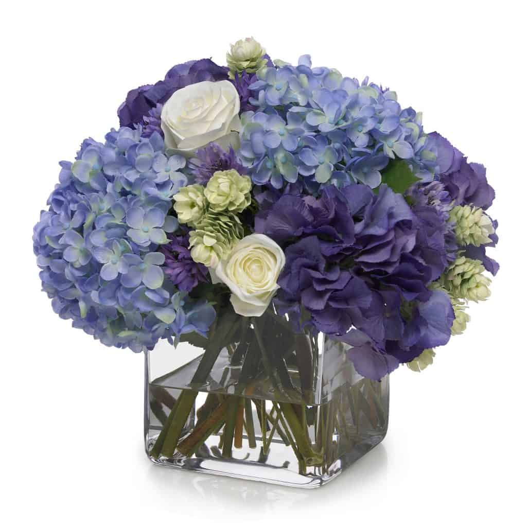 A beautiful Hydrangea and rose bouquet on a glass square vase on a white background