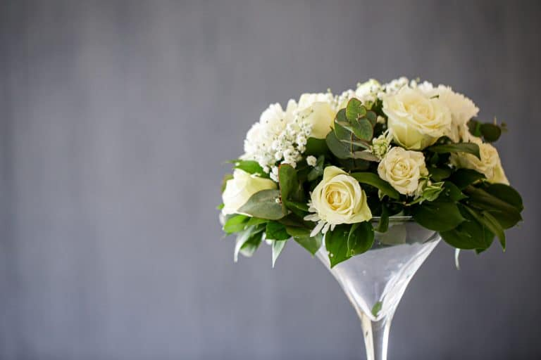 A bouquet of white roses in a large martini glass