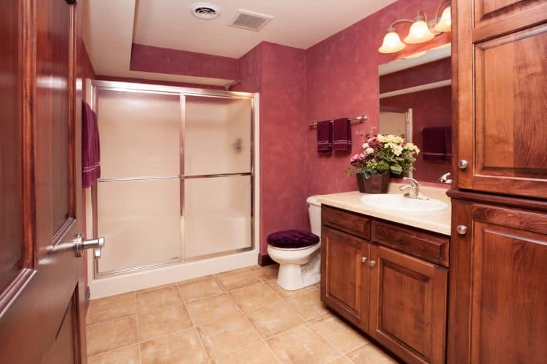A breathtaking basement with wooden cabinetry and a glass walled bathroom, How Big Should A Basement Bathroom Be?