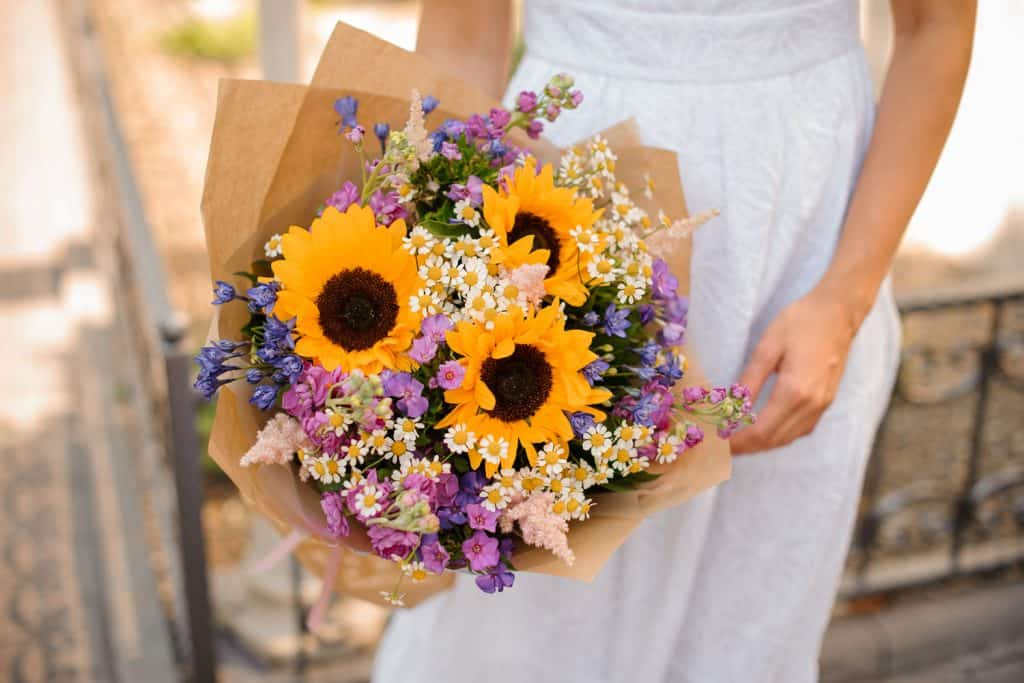 A bride holding a sunflower bouquet with other small flowers on the side
