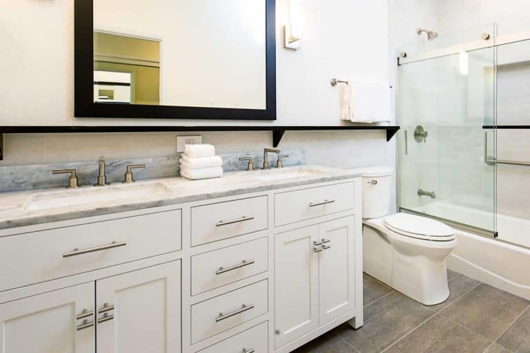 A contemporary modern bathroom design with bathtub, double sink vanity and mirror, What Kind Of Paint Should You Use On Bathroom Cabinets?