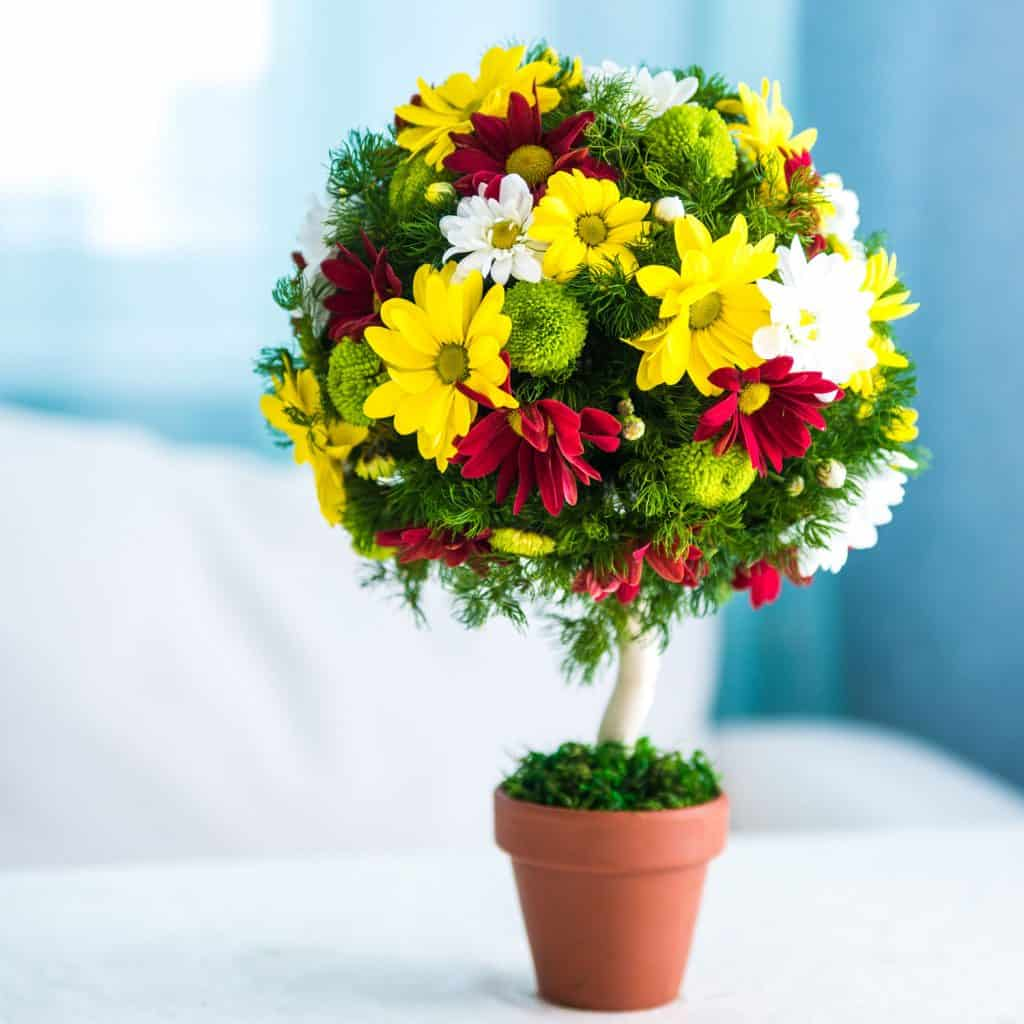 A decorative tree like design using margaritas, leaves, and chrysanthemums