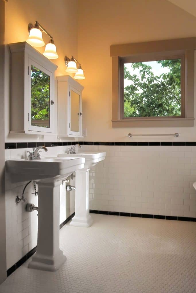 A dual sink bathroom with small cabinet mirrors and a square service window