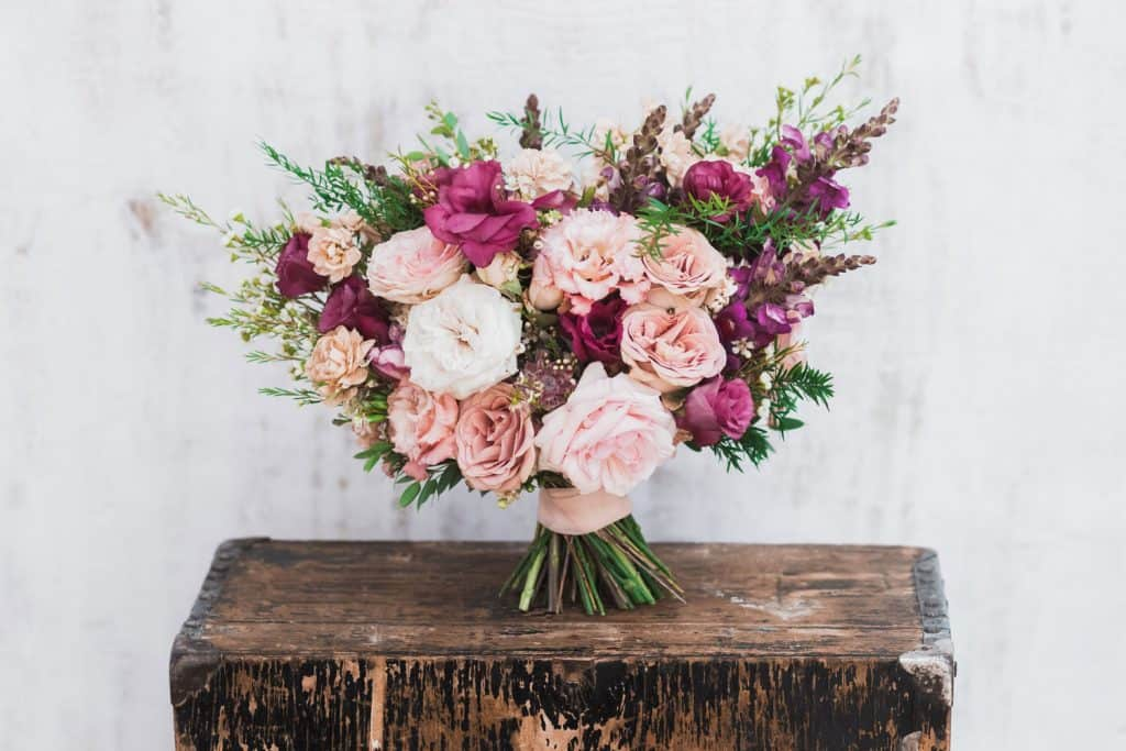 A fineart bouquet with pink, white, and violet roses on a wooden table