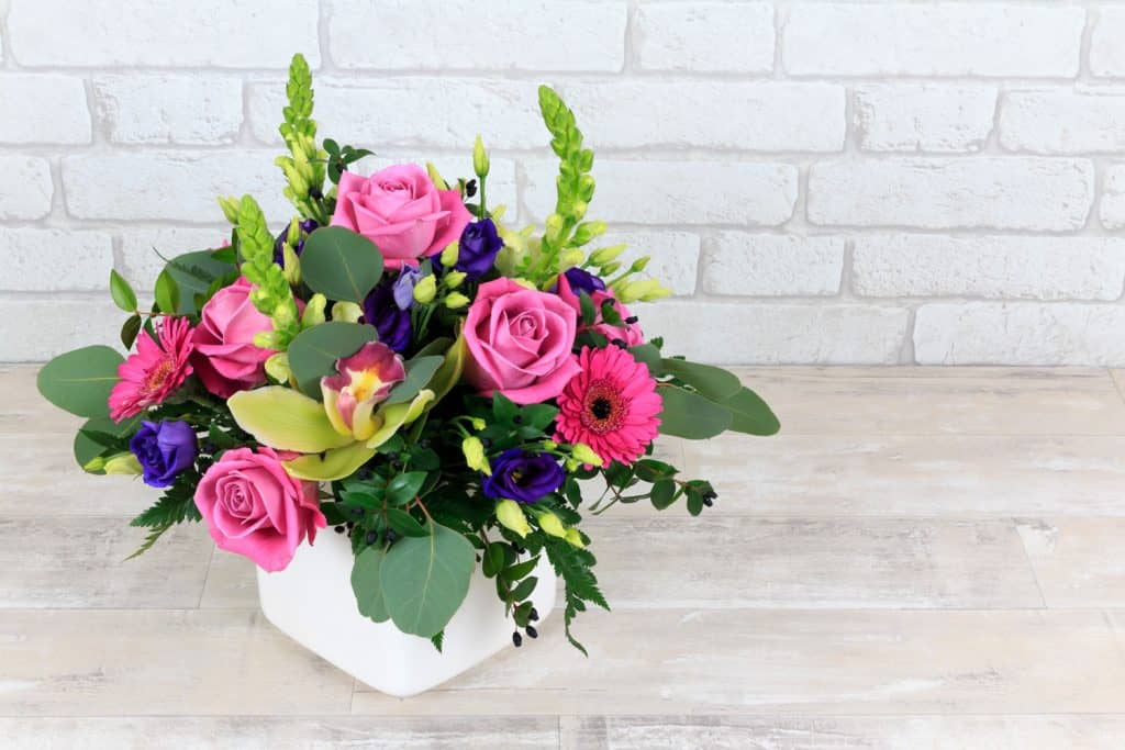 A gorgeous flower arrangement using pink flowers, leaves, and a white ceramic pot