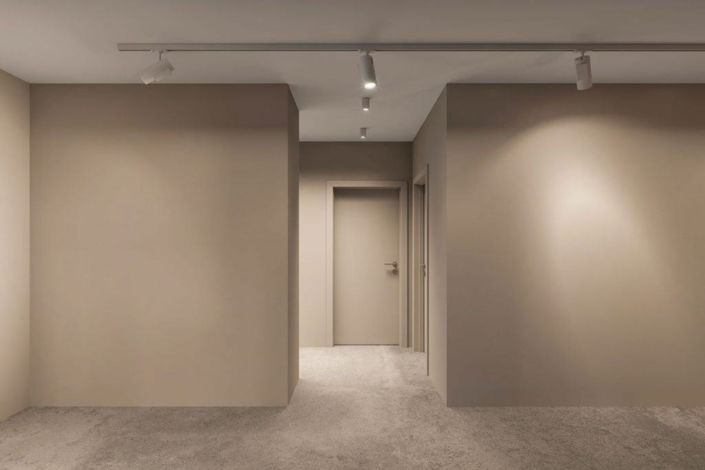 A gorgeous hallway with gray colored walls, carpeted flooring, and properly placed lighting